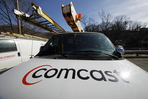 Photo - FILE - In this Tuesday, Feb. 15, 2011, file photo, a Comcast truck is parked in Pittsburgh.  Comcast Corp. reports quarterly financial results before the market opens on Wednesday, Oct. 30, 2013. (AP Photo/Gene J. Puskar, File)