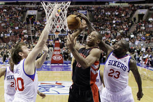 Photo -   Toronto Raptors' DeMar DeRozan, center, cannot get a shot past Philadelphia 76ers' Spencer Hawes, left, and Jason Richardson in the first half of an NBA basketball game, Tuesday, Nov. 20, 2012, in Philadelphia. (AP Photo/Matt Slocum)