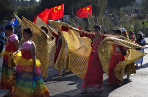 Photo -   Participants from China march during a parade where groups of Christians from various countries show their support for Israel in Jerusalem, Thursday, Oct. 4, 2012. Waving blue and white flags, thousands of Christians from around the world filled the streets of downtown Jerusalem on Thursday in a show of support for Israel that reflected the growing relationship between evangelical Christians and the Jewish state. (AP Photo/Sebastian Scheiner)