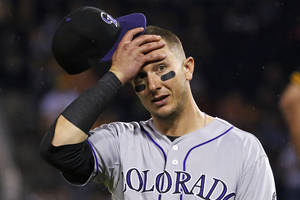 Photo - Colorado Rockies shortstop Troy Tulowitzki reacts to Pittsburgh Pirates' Starling Marte being hit in the head by a pitch from Rockies relief pitcher Adam Ottavino during the seventh inning of a baseball game in Pittsburgh on Friday, July 18, 2014. The Pirates won 4-2. (AP Photo/Gene J. Puskar)