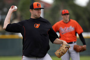 Photo - Baltimore Orioles pitcher Chris Tillman, left, throws to first after fielding the ball during a spring training baseball workout in Sarasota, Fla., Saturday, Feb. 15, 2014.  (AP Photo/Gene J. Puskar)