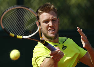 Photo - Jack Sock, of the U.S, slams a forehand to  Serbia's Dusan Lajovic during their third round match of  the French Open tennis tournament at the Roland Garros stadium, in Paris, France, Saturday, May 31, 2014. (AP Photo/Darko Vojinovic)