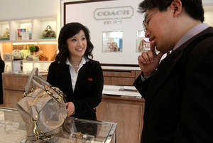 Photo - FILE -  In this file photo from Tuesday, May 19, 2009, Coach salesperson Pamela Li, left, shows bag to Yuji Matsumoto, of Japan, at a Coach store in San Francisco. <strong>Jeff Chiu - AP</strong>