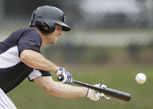 Photo - New York Yankees center fielder Brett Gardner bunts during spring training baseball practice Friday, Feb. 21, 2014, in Tampa, Fla. (AP Photo/Charlie Neibergall)