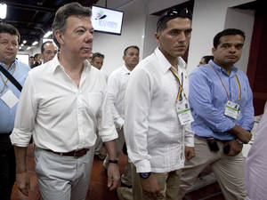 photo -   Colombia's President Juan Manuel Santos, left, visits the press room of the 6th Summit of the Americas in Cartagena, Colombia, Wednesday, April 11, 2012. Leaders of the western hemisphere will attend the meeting on April 15 and April 16. (AP Photo/Fernando Vergara)