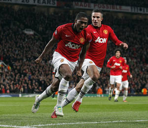 Photo - Manchester United's Antonio Valencia left, celebrates with team-mate Robin Van Persie after scoring the fourth goal of the game for his side during the Champions League Group A soccer match against Bayer Leverkusen, at Old Trafford in Manchester, England, Tuesday Sept 17, 2013. (AP Photo/Jon Super)