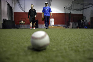 Photo - In this Feb. 24, 2014 photo, Kansas City Royals minor league pitcher John Walter, of Haddonfield, N.J., right, walks with Rob Potts, Program Director of  Power Train Sports Institute's AFC Baseball & Softball Academy in Cherry Hill, N.J. Potts is a 55-year-old former postal worker who spends his summers throwing batting practice to Chase Utley, Jimmy Rollins and Ryan Howard. When he's not at the ballpark, he's director of baseball operations at the baseball facility where several major and minor leaguers not only stay in shape during the winter, but hold pitching clinics for kids.  (AP Photo/Mel Evans)