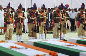 Photo - Indian security personnel pay homage to paramilitary soldiers killed in an ambush by Maoist rebels, in Jagdalpur, in the eastern Indian state of Chhattisgarh, Wednesday, March 12, 2014. Maoist insurgents will not be allowed to spoil next month's Indian elections with violent attacks, the home minister said Wednesday, a day after rebels killed 16 people in their deadliest raid in almost a year. (AP Photo)