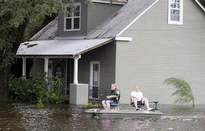 Photo -   Two men use small boat to travel though flooded streets Thursday, Aug. 30, 2012, in Slidell, La. Isaac's maximum sustained winds had decreased to 45 mph and the National Hurricane Center said it was expected to become a tropical depression by Thursday night. (AP Photo/John Bazemore)
