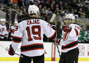 Photo - New Jersey Devils' Travis Zajac (19) is congratulated by teammate Damien Brunner (12), of Switzerland, after scoring in the second period of an NHL hockey game against the Dallas Stars, Thursday, Jan. 30, 2014, in Dallas. (AP Photo/Tony Gutierrez)