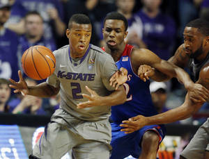 Photo - Kansas State guard Marcus Foster (2) tries to go around Kansas guard Andrew Wiggins, center, during the first half of an NCAA college basketball game in Manhattan, Kan., Monday, Feb. 10, 2014. (AP Photo/Orlin Wagner)