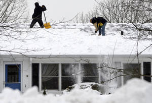 Photo - Two men clear snow off a roof of a home in North Andover, Mass. Monday, Feb. 11, 2013. Beleaguered Massachusetts residents returned to work on Monday for the first time since the weekend blizzard, crawling along narrow snow-covered secondary roads and being greeted by a new wintry mix of sleet and freezing rain. (AP Photo/Elise Amendola)