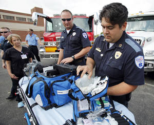 Photo - EMSSTAT paramedics Jason Carter, left, and Lemuel Finlay assemble equipment before loading it onto an ambulance. PHOTO BY STEVE SISNEY, THE OKLAHOMAN <strong>STEVE SISNEY</strong>