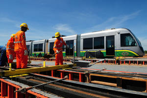 Photo - In this Nov. 13, 2013 photo released by Secom-MT, personnel work next to new trains in Cuiaba, Mato Grosso state, Brazil. The head of World Cup projects for Brazil's far-western Mato Grosso state has acknowledged the light rail system in the city of Cuiaba meant to help football fans move around the city during World Cup matches won't be ready in time for the 2014 World Cup. (AP Photo/Secom MT, Josi Pettengill)