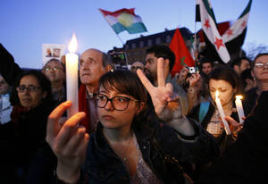 Photo - Protesters holding candles and waving flags gather during a rally to support the Syrian people on the first anniversary of the Syrian uprising in front of Paris City hall in Paris, Thursday March 15, 2012. (AP Photo/Francois Mori) ORG XMIT: XFM116