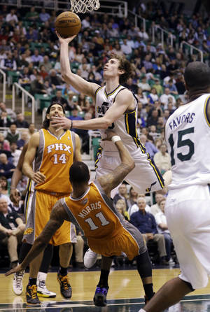 Photo - Phoenix Suns' Markieff Morris (11) fouls Utah Jazz's Gordon Hayward (20) as Suns' Luis Scola (14) watches during the fourth quarter of an NBA basketball game, Wednesday, March 27, 2013, in Salt Lake City. The Jazz won 103-88. (AP Photo/Rick Bowmer)