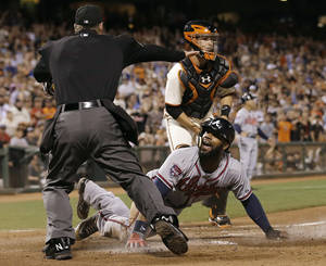 Photo - Atlanta Braves' Jason Heyward, bottom, is called safe at home by umpire Ed Hickox, left, in front of San Francisco Giants catcher Buster Posey during the sixth inning of a baseball game in San Francisco, Tuesday, May 13, 2014. Giants manager Bruce Bochy challenged the ruling but the play stood. The Braves won 5-0. (AP Photo)