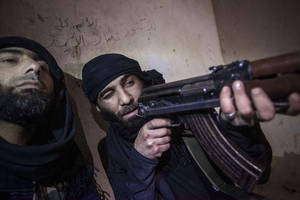photo - In this Wednesday, Dec. 5, 2012 photo, a Free Syrian Army fighter aims his weapon during heavy clashes with government forces in Aleppo, Syria. (AP Photo/Narciso Contreras)