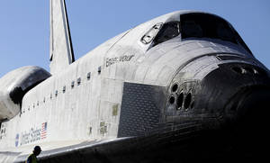 photo -   A workman helps in the process of prepping the space shuttle Endeavour to move the final few yards into a temporary hangar at the California Science Center in Los Angeles on Sunday, Oct. 14, 2012. After a 12-mile (19-kilometer) weave past trees and utility poles that included thousands of adoring onlookers, flashing cameras and even the filming of a TV commercial, Endeavour arrived at the California Science Center Sunday to a greeting party of city leaders and other dignitaries that had expected it many hours earlier. (AP Photo/Los Angeles Times, Luis Sinco, Pool)  