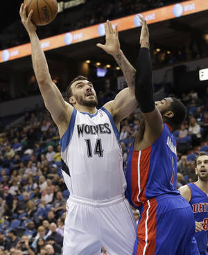 Photo - Minnesota Timberwolves' Nikola Pekovic (14), of Montenegro, lays up a shot as Detroit Pistons' Brandon Knight defends in the first quarter of an NBA basketball game, Saturday, April 6, 2013, in Minneapolis. (AP Photo/Jim Mone)