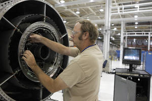 Photo - TINKER MAINTENANCE FACILITIES: Richard Law inspects an aircraft engine core with a scope at Tinker Air Force Base in Midwest City, Tuesday, July 3, 2012.  The Oklahoman Archives