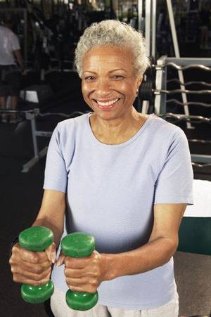 Photo - Senior woman weight training in gym, smiling, portrait
