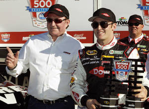 Photo - Austin Dillon, right, holds up the pole award with car owner and grandfather Richard Childress after qualifying for the pole position in the Daytona 500 NASCAR Sprint Cup Series auto race at Daytona International Speedway in Daytona Beach, Fla., Sunday, Feb. 16, 2014. (AP Photo/Terry Renna)