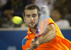 Photo - Marin Cilic, of Croatia, returns the ball to Kevin Anderson during the Delray Beach Open tennis tournament, Sunday, Feb. 23, 2014, in Delray Beach, Fla. Cilic won 7-6 (6), 6-7 (7), 6-4.  (AP Photo/J Pat Carter)