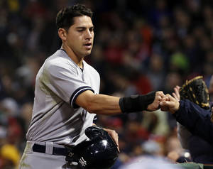 Photo - New York Yankees' Jacoby Ellsbury receives a fist-bump after scoring on a single by Derek Jeter during the fifth inning of a baseball game against the Boston Red Sox at Fenway Park in Boston, Tuesday, April 22, 2014. (AP Photo/Elise Amendola)