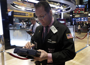 Photo - Trader Edward Curran works on the floor of the New York Stock Exchange Wednesday, Jan. 8, 2014.Stocks are mostly lower in early trading as investors hold back ahead of the release of the latest news from the Federal Reserve. (AP Photo/Richard Drew)