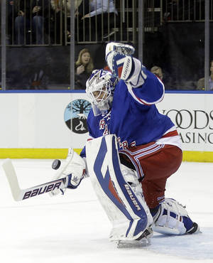 Photo - New York Rangers goalie Henrik Lundqvist, of Sweden, stops a shot on the goal from Carolina Hurricanes' Alexander Semin during the first period of an NHL hockey game Tuesday, April 8, 2014, in New York. (AP Photo/Frank Franklin II)