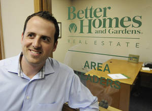 "Photo -   In this Tuesday, Oct. 9, 2012 photo, Andy Asbury, owner of ""Better Homes & Gardens Real Estate Area Lenders"", is shown at his office in Edina, Minn. Asbury, who has the business to support more agents, hired a full-time employee just last Friday. Asbury said his sales are up 25 percent from a year ago and he's expecting them to rise further next year. (AP Photo/Jim Mone)"