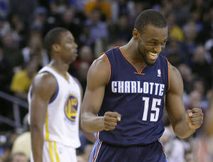 Photo - Charlotte Bobcats' Kemba Walker (15) celebrates after scoring against the Golden State Warriors during the second half of an NBA basketball game in Oakland, Calif., Tuesday, Feb. 4, 2014. The Bobcats won 91-75. (AP Photo/Tony Avelar)