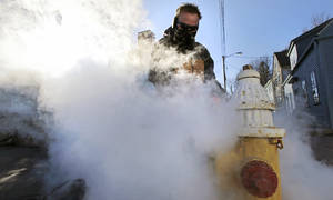 photo - Jon Gilbert, of the Portsmouth, N.H. water department, steams a frozen hydrant in Portsmouth, N.H., Wednesday, Jan. 23, 2013.  Temperatures in New Hampshire hovered close to single digits, with wind chill temperatures going below zero for most of the day. (AP Photo/Charles Krupa)