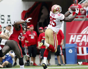 Photo - San Francisco 49ers tight end Vernon Davis (85) pulls in a 52-yard touchdown reception after getting past Tampa Bay Buccaneers strong safety Mark Barron (23) during the second quarter of an NFL football game, Sunday, Dec. 15, 2013, in Tampa, Fla. (AP Photo/Reinhold Matay)