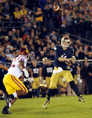 Photo - Notre Dame quarterback Tommy Rees throws a pass as Southern California linebacker Devon Dennard closes during the first quarter of a college football game on Saturday, Oct. 19, 2013, in South Bend, Ind. (AP Photo/Joe Raymond)