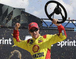 Photo - Joey Logano celebrates after winning the NASCAR Sprint Cup series Pure Michigan 400 auto race at Michigan International Speedway in Brooklyn, Mich., Sunday, Aug. 18, 2013. (AP Photo/Paul Sancya)