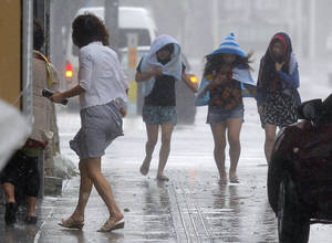 Photo - Women walk amid strong winds on a street in Naha, Okinawa, southern Japan, Tuesday, July 8, 2014. Powerful Typhoon Neoguri pounded across the southern Japanese islands of Okinawa on Tuesday, as residents took refuge from destructive winds, towering waves and storm surges. Airports closed and residents were evacuated from low-lying areas and shorelines as the typhoon passed over Okinawa, packing sustained winds of 175 kilometers (108 miles) per hour and gusts up to 250 kph (154 mph), the Japan Meteorological Agency said. (AP Photo/Kyodo News) JAPAN OUT, CREDIT MANDATORY