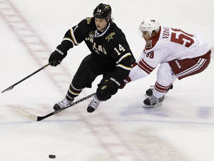 Photo - Dallas Stars' jamie Benn (14) and Phoenix Coyotes center Antoine Vermette (50) compete for a loose puck in the third period of an NHL hockey game on Friday, Feb. 1, 2013, in Dallas. The Stars won in a shootout 4-3. (AP Photo/Tony Gutierrez)