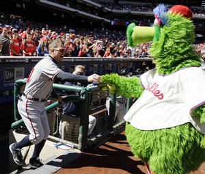 Photo -   Atlanta Braves' Chipper Jones, left, laughs as he returns keys to the Philadelphia Phillies mascot, the Phillie Phanatic, after Jones stole them from the Phanatic's all-terrain vehicle before a baseball game between the Phillies and Braves, Sunday, Sept. 23, 2012, in Philadelphia. (AP Photo/Matt Slocum)