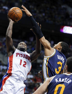 Photo - Detroit Pistons guard Will Bynum (12) takes a shot against Utah Jazz guard Trey Burke (3) during the first half of an NBA basketball game Friday, Jan. 17, 2014, in Auburn Hills, Mich. (AP Photo/Duane Burleson)