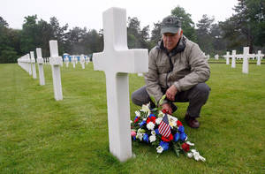 Photo - Paul Clifford, 70,  from Boston MA, USA, places flowers on the grave of Walter J. Gunther Jr, the uncle of his best friend, in the Normandy American Cemetery and Memorial, in Colleville sur Mer, France, Wednesday June 4, 2014.  World leaders and veterans prepare to mark the 70th anniversary of the D-Day invasion this week in Normandy. (AP Photo/Claude Paris)