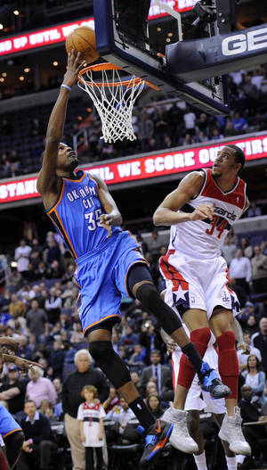 Photo - Oklahoma City Thunder forward Kevin Durant (35) goes to the basket against Washington Wizards center JaVale McGee (34) during the first half of an NBA basketball game on Wednesday, Jan. 18, 2012, in Washington. (AP Photo/Nick Wass) ORG XMIT: VZN101