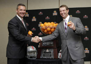 Photo - Ohio State head coach Urban Meyer, left, and  Clemson head coach Dabo Swinney pose for photographers with the Orange Bowl trophy in Fort Lauderdale, Fla., Thursday, Jan. 2, 2014. Ohio State will face Clemson in the NCAA college football Orange Bowl classic, Friday, Jan. 3, in Miami Gardens, Fla. (AP Photo/Alan Diaz)
