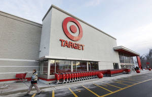 Photo - FILE - In this Dec. 19, 2013 file photo, a passer-by walks near an entrance to a Target retail store in Watertown, Mass. Target on Friday, Dec. 27, 2013 said that customers' encrypted PIN data was removed during the data breach that occurred earlier this month. But the company says it believes the PIN numbers are still safe because the information was strongly encrypted. (AP Photo/Steven Senne, File)