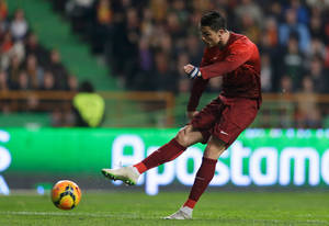 Photo - Portugal's Cristiano Ronaldo shoots to score the opening goal during their friendly soccer match with Cameroon Wednesday, March 5 2014, in Leiria, Portugal.  The game is part of both teams' preparation for the World Cup in Brazil. (AP Photo/Armando Franca)