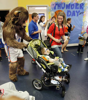 "photo - Oklahoma City Thunder mascot Rumble pushes Kannon Foster, 2, in a stroller Thursday while his mother, Kelli, watches at a ""Thunder Appreciation Day"" at the J.D. McCarty Center in Norman. PHOTO BY STEVE SISNEY, THE OKLAHOMAN <strong>STEVE SISNEY</strong>"