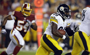Photo - Pittsburgh Steelers running back Le'Veon Bell (26) runs as he pursued by Washington Redskins linebacker Darryl Tapp (54) during the first half of an NFL preseason football game against the Washington Redskins, Monday, Aug. 19, 2013, in Landover, Md. (AP Photo/Alex Brandon)
