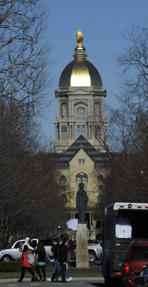 Photo - FILE - In this Jan. 17, 2013 file photo, people walk in front of the Notre Dame administration building, known as the Golden Dome, on the campus of the University of Notre Dame in South Bend, Ind. The University of Notre Dame is suing the Obama administration over a federal mandate that its health insurance plans for students and employees cover birth control. The university filed its lawsuit Tuesday, Dec. 3, 2013, in U.S. District Court in South Bend.  (AP Photo/Joe Raymond, FILE)