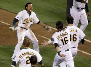 Photo -   Oakland Athletics left fielder Coco Crisp (4) celebrates after he hit single to score Seth Smith and win the game 4-3 in the ninth inning of Game 4 of an American League division baseball series against the Detroit Tigers in Oakland, Calif., Wednesday, Oct. 10, 2012. (AP Photo/Eric Risberg)